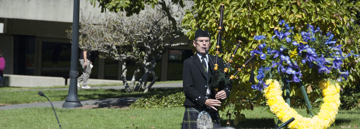 Photo of bagpipe player at campus memorial next to wreath of yellow and purple flowers
