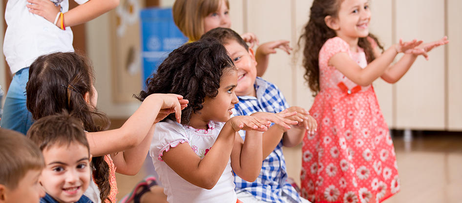 Group of children sitting and standing around clapping hands and dancing