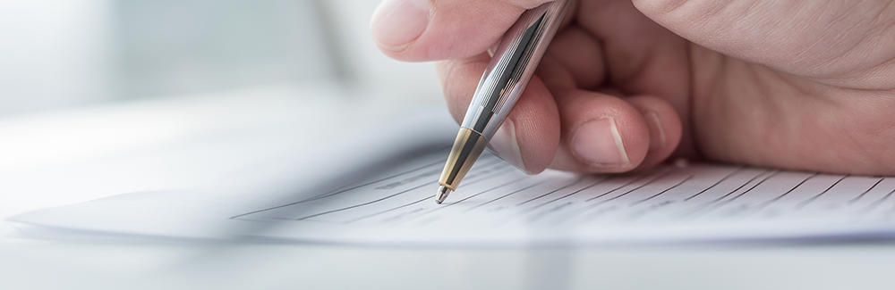 Image of hand signing paperwork with pen