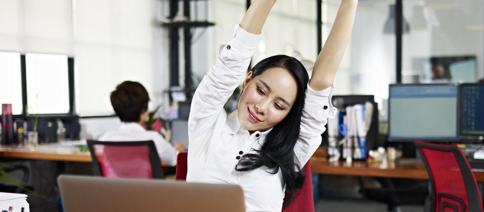 Image of women stretching while looking at a laptop
