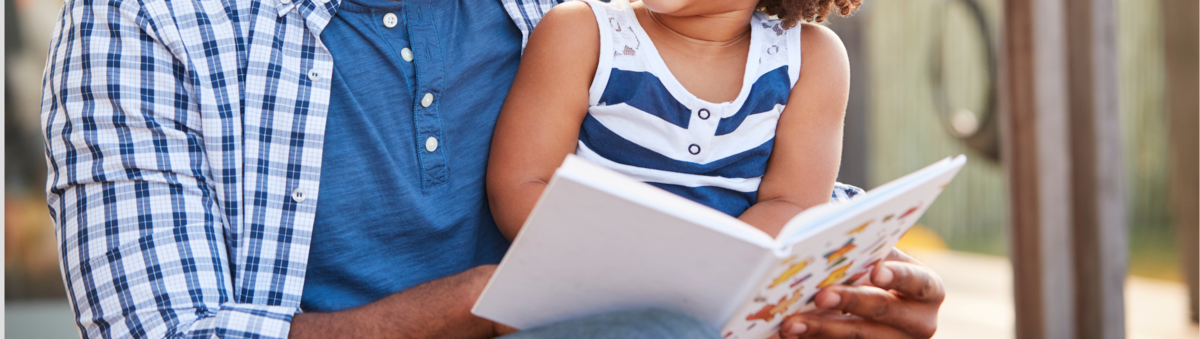 Black father reading with daughter