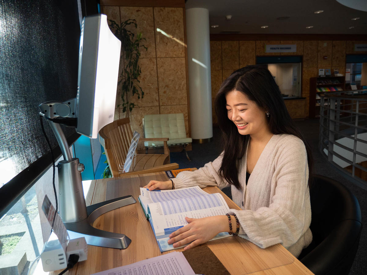 female student reading a book while using light therapy lamp