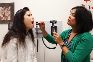 doctor checking student's mouth with light and tongue presser