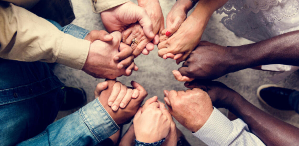 Hands reaching together in a circle to join and be together.