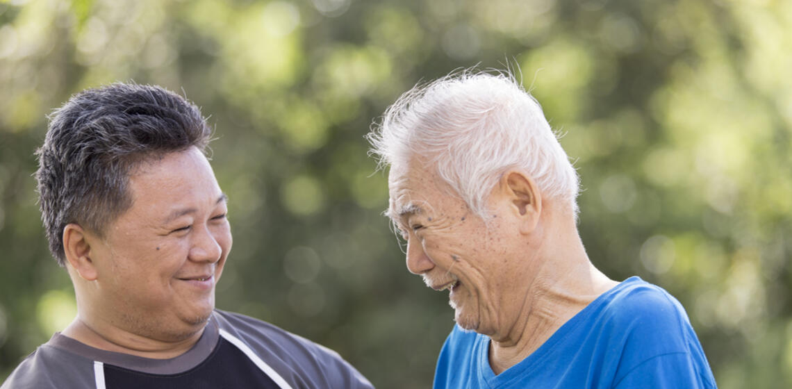 Elderly Asian man laughing with a younger Asian man