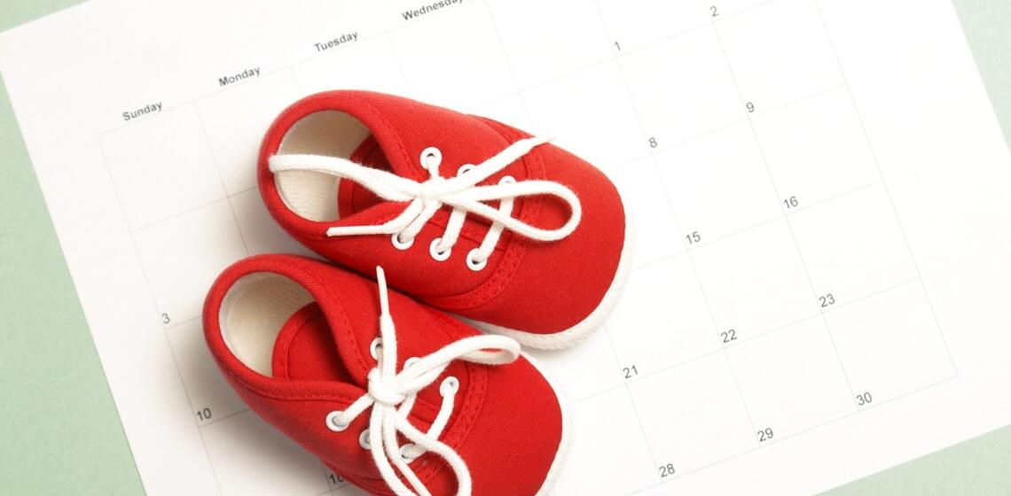 A pair of red baby shoes sitting over a calendar