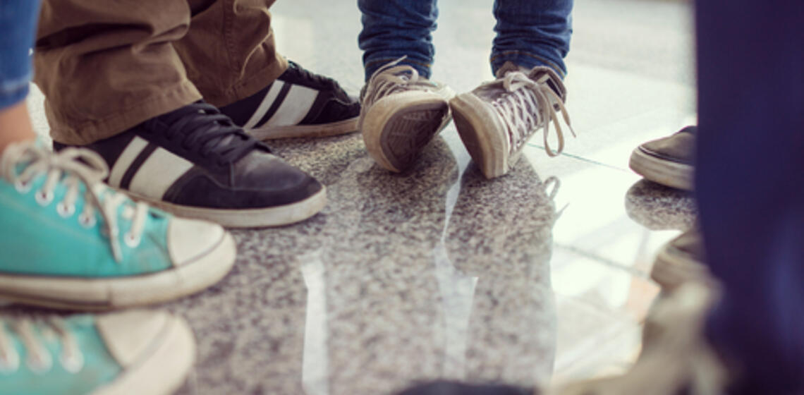 View of Young people's shoes as they stand in a circle