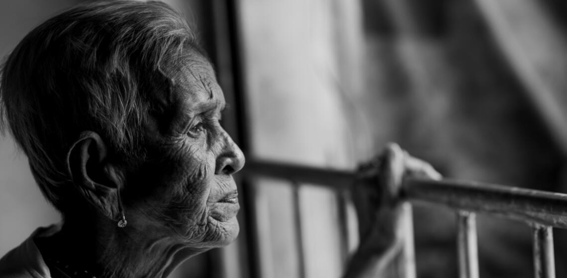 Black and white photo of a woman looking over the railings of a balcony forlornly
