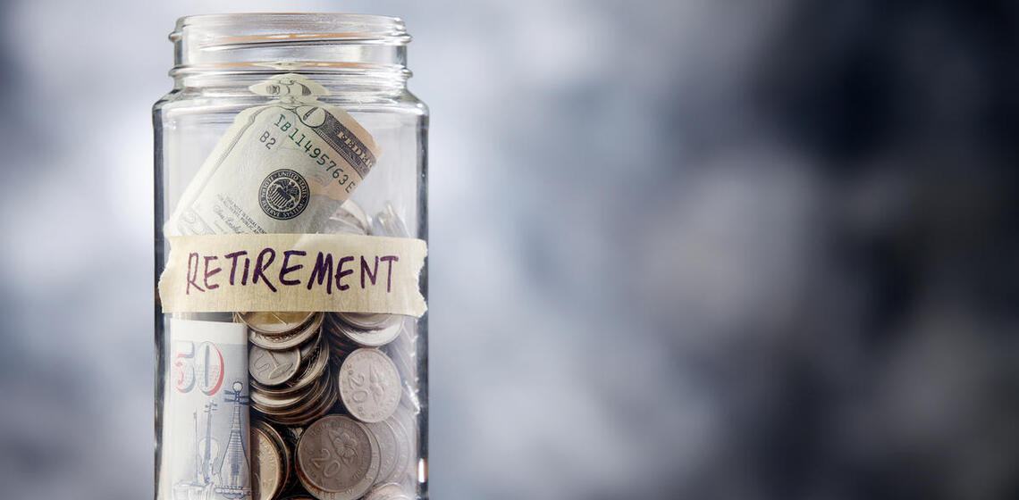 A jar filled with coins that has a label which reads 'Retirement Fund'