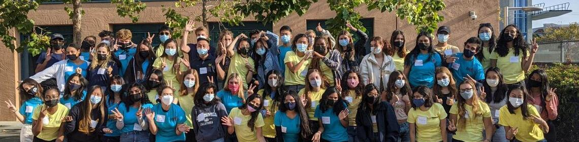 Health workers wearing masks and making silly poses in front of trees at Tang Center