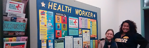 """Two female Health Workers smiling next to a bulletin board that says """"health worker"""""""