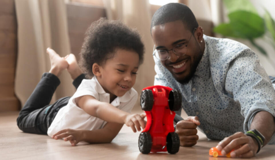 A Black man and young child lying on their stomachs on the floor smiling and playing with a red toy car