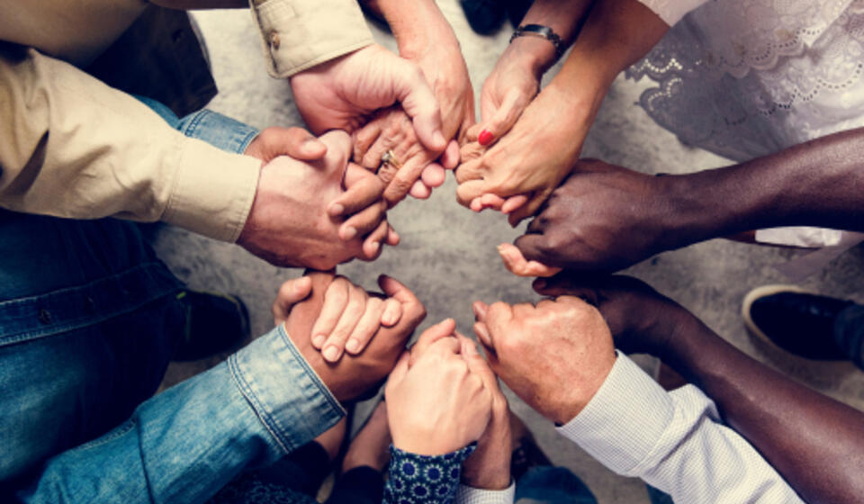 Close Photograph of five people in a circle holding hands in support of each other