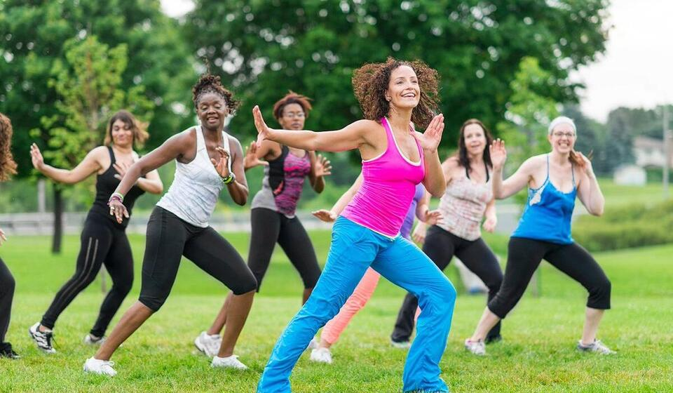 group of people doing a dance workout outside