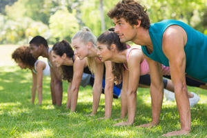 photo of young adults doing push ups
