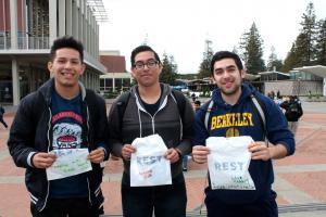 Photo of three students showing off their new REST Zone campaign bags